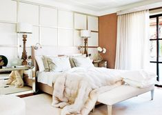 All-white bedroom with mirrored nightstands and fur blanket