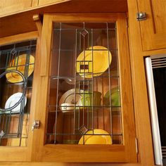 Handcrafted leaded-glass cabinet door panels show off dishware and reflect light back into the kitchen