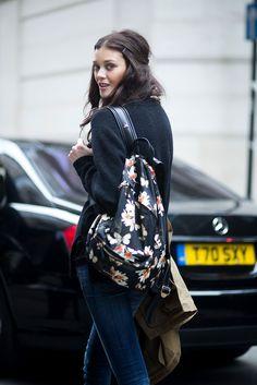 La modelo Diana Moldovan en un look de abrigo negro, denim y mochila con estampado de flores, saliendo del desfile de Matthew Williamson otoño-invierno 2015 durante London Fashion Week.