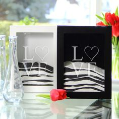 """Add a modern twist to your wedding with this sand ceremony shadow box set. Featuring a contemporary look, this shadow box has the word """"Love"""" etched on the glass facing and a sleek wooden frame. Two accompanying side vases for sand pouring are included."""