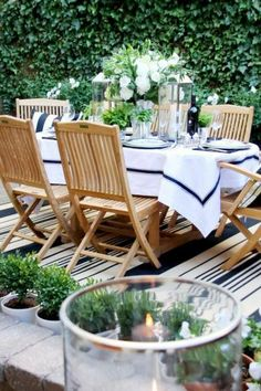 Outdoor dining party with blue and white striped rug, wood patio chairs and a blue and white table setting surrounded by a row of tiny boxwood trees and a wall of ivy