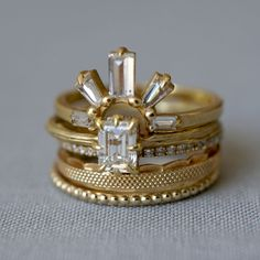 Every morning is good with the Evangeline Stack! Featuring one of our favorite nesting bands ever, the Diamond Sunrise Ring hugs the Artemis solitaire creating a playful yet modern take on the wedding ring stack. Mixtures of beaded gold and lace-like embellishments keep the overall feel light, airy and elegant.