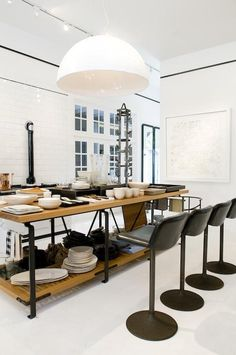 A custom oak and steel table has a rail at one side for hanging utensils