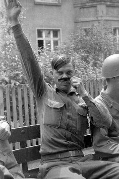 A U.S. soldier mocks Hitler for the camera, World War II.