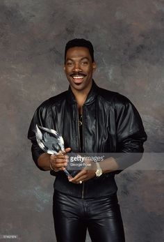 Actor and comedian Eddie Murphy poses with his People's Choice Award in a 1989 backstage Beverly Hills, California telecast photo shoot. Eddie Murphy, Comedians, Awards, Leather Jacket, Photoshoot, Poses, Actors, People, Beverly Hills