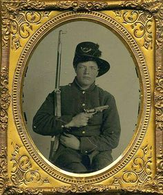 A splendid sixth-plate ambrotype of a double-armed Federal infantryman. Seated pose dressed in his frock a sporting this wonderful M1858 Hardee hat with an ostrich plume and infantry insignia pinned to the front. His musket is tucked under his arm with the bayonet attached while he displays a nice Colt 1849 pocket revolver across his chest. This image is housed in a very nice double sided thermoplastic case.