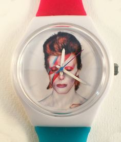 Glam out Bowie style with this Aladdin Sane wrist watch! Youll be singing Rebel Rebel as you look down at this watch during your boring office meeting! Hes looking extra pale and alien like in this image, which is fabulous. This plastic unisex watch with silicon band measures 10 long and approx. 1.75 in diameter. Watch is water resistant but not water proof