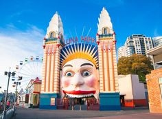 Large colourful clown-like face and towers guarding the entrance to amusement park on the water's edge, with Ferris wheel and other rides in the background.