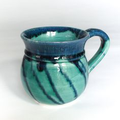"Glazed with an aqua Green Shiny Turquoise glaze and a blueberry syrup on the lips and handle, this wheel-thrown coffee cup is great for enjoying your coffee and tea drinking too! 4"" high by 3.5"" wide"