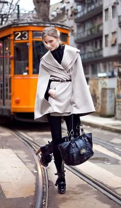 beige cape coat over black skinny jeans and super-sized handbag