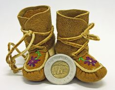 Miniature Caribou Wrap Around Moccasins with embroidered flower. Made by a Tlicho from Whatì, Northwest Territories, Canada.