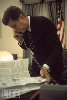 President Kennedy reading the newspaper while talking on the phone.