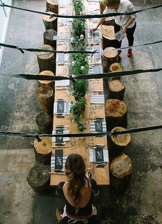 Mesa con bancos. Individuales escritos con tiza. Centro de mesa único y alargado. Rústico bonito.