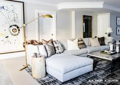 Beautifully designed transitional living room boasts a long gray sofa topped…