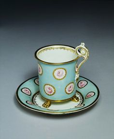 Cup Place of origin:   Swansea, Wales (made)   London, England (decorated)    Date: 1817-1820 (made)   Artist/Maker:    Billingsley, William, born 1758 - died 1828 (maker)    Powell, John (decorator)  Materials and Techniques:    Porcelain, painted in enamels and gilt  Credit Line:    Bequeathed by Joseph Henry Jacobs. Museum number:    C.48 wide, plain surfaces of such chocolate cups and stands of French 'Empire' style were ideal for displaying elaborate enamel painting.  V