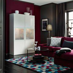 Woonkamer met opbergcombinatie in hoogglans wit met deuren in frosted glas, en rood-paarse 2-zitsbank met chaise longue, in combinatie met hoogpolig vloerkleed met ruitenmotief in grijs, rood-paars, wit, turkoois en blauw