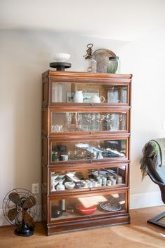 "A glass-fronted barrister bookcase—found at an antiques shop near Belfast, Maine—holds Nakazato's ceramics mixed with glassware. ""It's rare to find a barrister bookcase so tall, and we knew it would be perfect for stemware or special pieces that might prefer a little more protection,"" Nakazato says. ""Maine is far enough away from urban centers that you can still find many antique and vintage gems at reasonable prices."""