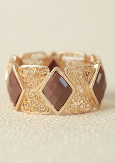 Maharini Stretch Bracelet 15.99 at shopruche.com. Toffee-colored diamond-shaped pendants adorn this intricately patterned gold-toned stretch bracelet. Pair this gorgeous bracelet with any earth-toned outfit for added gleam.
