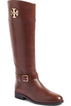 A gleaming logo medallion adds signature shine to this tall, lustrous leather riding boot girded at the ankle with an adjustable buckled strap.