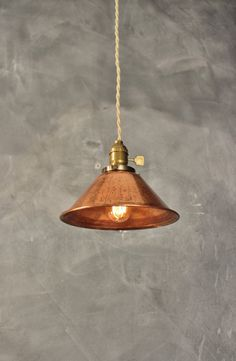A simple, smart-looking vintage style pendant light with a weathered copper cone lamp shade. Matched with an antique style lamp socket with an aged brass finish and a flat paddle switch. Includes 7 feet of brand new cloth-wrapped twisted cord with an industrial style wall plug. (Cord color