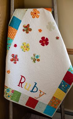 This colorful baby girls patchwork quilt offers the ultimate in style and comfort for your little one. Custom handmade in loving detail, it features a white center with bright patchwork blocks along the borders and colorful, floral fabric appliques in the center. The back is a vibrant fabric that is ideal for a little girl! Your babys name will be customized on the front and a special tag with you very own note can be created for the back. This also makes an excellent gift idea for a new…