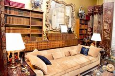 A neutral sofa, ornate accessories, and a full bookshelf in Coco Chanel's apartment