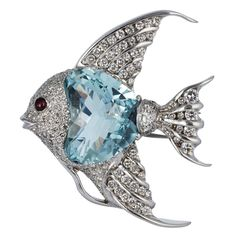Aquamarine & Diamond Fish Pin _     18 karat white gold angelfish pin consisting of of one fantasy cut aquamarine weighing approximately 24.00 carats, channel and pave set round brilliant cut diamonds having an approximate total weight of 8.00 carats and a single cabochon ruby eye.