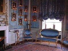 Rococo Style drapery in this English Warwick House is a good example of Italian influence with a balloon or roman shade style valance. It is gathered with yards of silky blue floral fabric tied back to create folds and curves to coordinated color scheme with the blue sofa and chairs as well as the light blue fabric walls contrasting the white wainscoting and moldings.