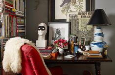 """Michael's """"home office"""" centers on a spindle-leg table flanked by a masked bust and a Bunny Williams Home lamp. The black-and-white photograph of a lifeguard, a work by photographer Matt Albiani, leans against a wall painted in Glidden's Ascot Blue."""