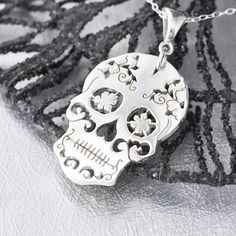 Sterling Silver Sugar Skull Pendant A hand cut beautiful piece! This Sugar Skull is made by carefully sawing and cutting the design into the thick sterling silver sheet. We the sand and polishing the piece to a high reflective shine :) Each skull is uniquely made to order, so please allow a few days before we ship. Its delicate work, but a very substantial piece. The pendant is 1.3mm thick and measures a little over an inch in length. This piece includes the chain - we have 16, 18 and 20…