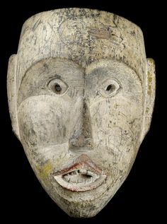 Indonesia, Borneo (Kalimantan), Bahau Dayak: A mask.  A very unusual old mask of Bahau Dayak made of heavy, hard wood (usually the Bahau masks are carved from lightweight, light-coloured wood). Of typical form with heart-shaped face, small eyes with pierced pupils, long ears and an accentuated forward-protracted, pointed and open mouth with teeth. The whole mask is secondarily painted in white. Underlaid with an older black ground and a very old patina (also inside!).