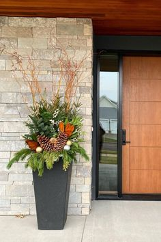 Leverage the incredible 3-ft height of this Sonata planter to create grand scale in a modern winter planter arrangement! Here, container design expert June Spanier layered pine branches, spruce, and cedar boughs with pine cones, curly willow and white winter berry. To match the height of this modern front door, the greeny is placed vertically and willow reaches for the roof. The magnolia perfectly coordinates with the wooden door! Photo credit: June Spanier Winter Planter, Curly Willow, Floors And More, Modern Front Door, Self Watering Planter, Plastic Planter, Outdoor Material, Container Design, Recycled Rubber
