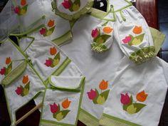 kit de cozinha bordado com tulipas coloridas e barrado de listradinho. Feito em tricoline branca e tem 12 peças.  Preços de cada item que compõe este kit:  puxa saco - R$ 23,00 bate mão - R$ 25,00 porta papel toalha - R$ 20,00 porta pão - R$ 28,00 pano de prato - R$ 18,00 protetor de alimentos - R$ 18,00 toalha p/ fogão - R$ 28,00 porta assadeira R$ 30,00 capa p/ botijão de gás - R$ 27,00 capa p/ galão de água - R$ 23,00 puxa bombril - R$ 14,00 toalha/puxador geladeira - R$ 12,00  Acompanha…