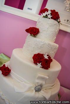 Torta nuziale con decorazione in pizzo, camei, fiocco e spilla. Ad ultimare il decoro rose rosse in pasta di zucchero
