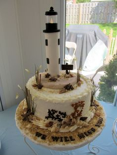 "St. Simons Island Lighthouse - This cake was for my little sister and brother-in-law's going away party.  They have retired and are moving to St. Simons Island, Georgia.  St. Simons is known for their lighthouse.  I hope I did it justice!  Their really loved the cake and that is what is most important to me!  The cake is a 10"" Mounds Bar cake with Buttercream icing.  The decorations are white and milk chocolate.  I made the dune fencing by hand.  Thanks to tokazodo!  Her beautiful beach cake..."