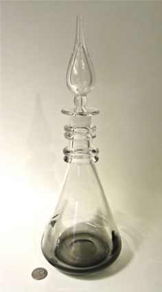 "Erickson ""Flame"" Decanter (Charcoal Gray) In addition to this rarer uncolored (clear) variation, Erickson also made these flame decanters in a number of colors. Subtle tinting was added towards the bottom of the vessel in various colors—including charcoal gray, amethyst, and, of course, emerald:"