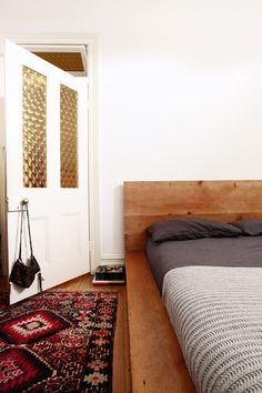 """In comparison to the rest of our home, our bedroom is quite simple with not much decoration. Our bed was made by a good friend as a wedding gift which makes it very special and the rug was bought while traveling through Turkey."""