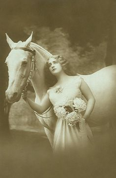 Vintage, lady posing with flowers and beautiful horse.