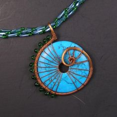 La Mer Turquoise Wire Wrapped Pendant and Beadwoven Necklace   Gorgeous big and bold wire wrapped pendant of Summer-y blue turquoise stone donut wrapped in copper wire with green glass miyuki drop bead spine. Spiral stiched rope necklace in blue and green with coordinating copper clasp necklace also made by me. Necklace measures 19 inches and is not adjustable. Pendant hangs 2 1/4 inches and is 2 inches wide.