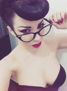 A modern retro vintage pin-up rockabilly beauty look, red lips, pale skin, cateye frames and perfect shiny hair