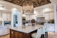 This spacious kitchen features all-over white cabinets that serve as a gorgeous contrast to a gray mosaic tile vaulted ceiling. An elegant chandelier enclosed in a glass cylinder hangs over the kitchen island, while white and light blue upholstered pub-style chairs provide casual dining space.