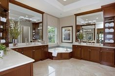 Large mirrors and glass-front cabinets adjoin dual sinks in this sleek master bath. The Magnolia Model from GL Homes. The Preserve at Bay Hill new home community. West Palm Beach, FL.