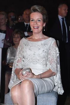 The white dress was covered by an elegant matching lace shawl, which kept the royal's shou...