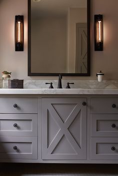 Chic cabin bathroom boasts a gray washstand adorned with gray x doors adorned with star knobs topped with calcutta marble countertop fitted with single bowl sink and oil-rubbed bronze faucet under black vanity mirror illuminated by Restoration Hardware Grand Edison Caged Sconces in Gunmetal Finish.