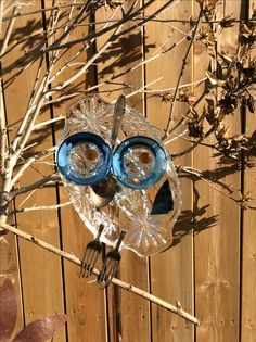 little blue glass owl, sits on a copper pole. made from vintage glass and cutlery