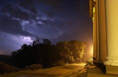 A Western Michigan University student watches an early morning lightning storm on the back steps of the historic East Hall on WMU's East Campus in Kalamazoo.  (Photo ©Mark Bialek)