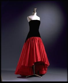 c1986: Evening dress: Murray Arbeid: Black silk velvet strapless evening dress with a fitted sheath bodice and drop-waisted full skirt in red taffeta: V&A T.672-1996 This dress was given to the V&A by the designer. An identical dress to this was worn by Diana, Princess of Wales.
