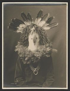 Title: Haschogan (House God) – The Yebichai Hunchback Date Created/Published: [1904] Summary: Photograph shows a Navajo man, half-length, seated, facing front, wearing a ceremonial mask with feathers and with fir or spruce branches forming a wreath around the shoulders.