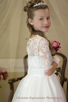 Classic style first communion dress with lace bodice and three quarter sleeves.  New for first communion season 2015 . This first communion gown is available exclusively through Christian Expressions. http://www.firstcommunions.com/first-communion-dresses-8021.aspx