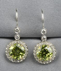 Fine Jewelry - Sale 2586B - Lot 629    18kt White Gold, Peridot, and Diamond Earpendants, each set with a circular-cut peridot measuring approx. 8.10 mm, framed and suspended by full-cut diamond melee, lg. 1 1/4 in.  Sold for $1,126.00